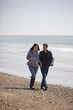 A pregnant woman and her partner walking on the beach