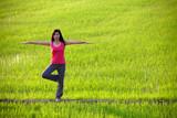 girl practicing yoga,standing in paddy field