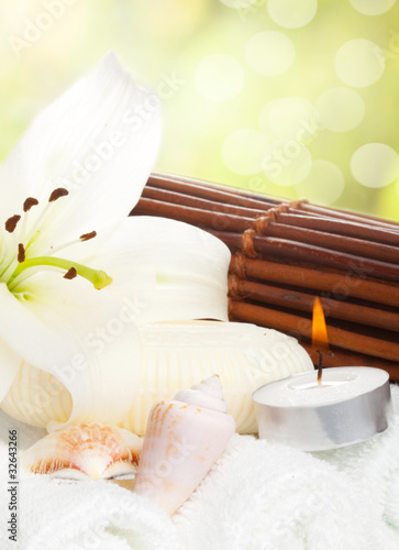 Flower, candle and soap on soft white towels