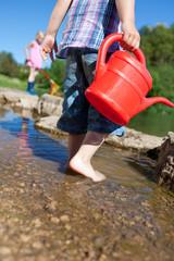zwei kinder spielen am wasser