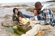 Young family with fishing net on rocks