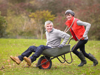 Young couple playing in wheelbarrow