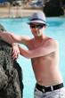 Porträt einer schönen jungen Mann in den Pool mit Hut