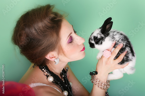 portrait of young beautiful girl with long hair and small rabbit