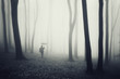 man with umbrella walking in a dark forest with fog