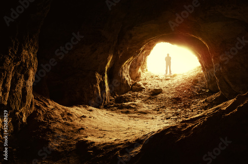 man standing in front of a cave entrance - 32682829