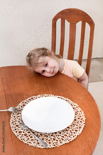 Little child sitting along at table with empty plate