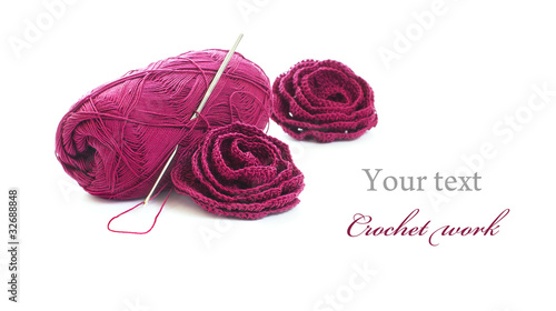 Crochet work: skein of yarn, crochet hook and crocheted roses