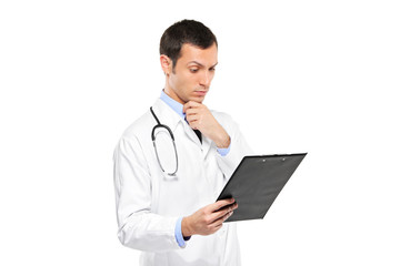 A portrait of a pensive medical doctor looking at clipboard