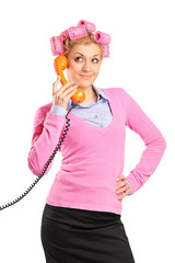 Young woman with hair rollers gossiping on a phone