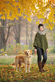 Young girl and her dog walking in autumn