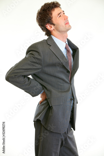 Young businessman holding hand at his aching back