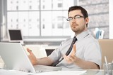 Young stock broker using laptop gesturing poster