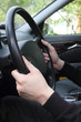 Close-up of male hands on steering wheel in a modern car