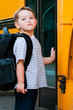 Defiant young boy in front of yellow school bus
