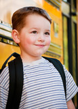 Content young boy in front of yellow school bus waiting