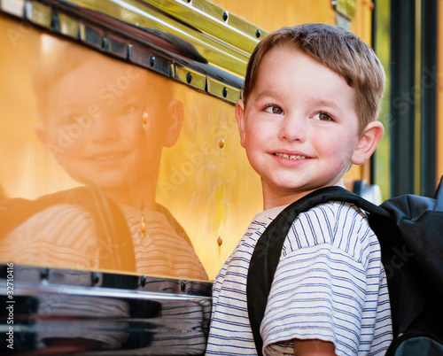 Young boy with nervous smile waits to board school bus