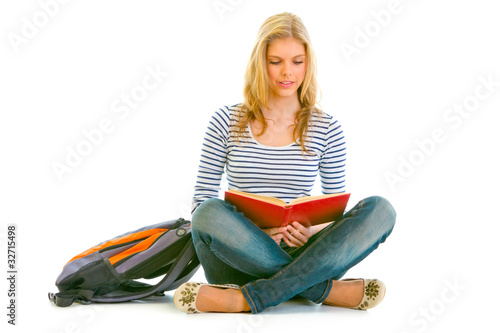 Pensive girl with schoolbag sitting on floor and reading book
