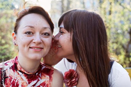 Young beautiful woman whispers something to girlfriend in ear