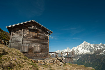 Mountain refuge house in French Alps under blue sky.