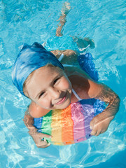 Swimming girl in blue water