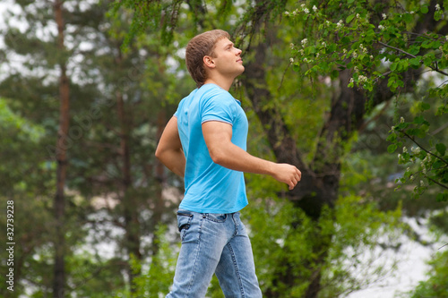 Young man running through park
