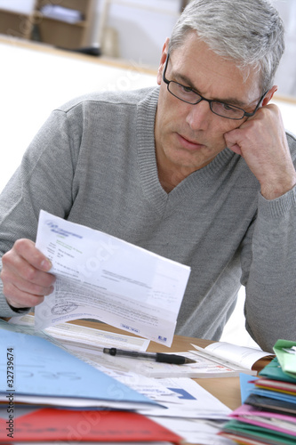 Particulier penché sur les  factures et charges