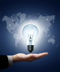 Light bulb in hand businessman on world map blue background.