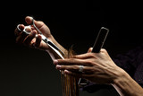 A close-up of hairdresser's hands cutting hair - 32743828