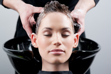 Beautiful young woman getting a hair wash. In a hair salon