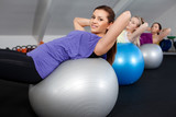 Attractive young women doing sit ups at a fitness club