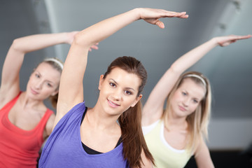 Three beautiful young woman stretching in aerobics class