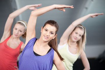 Three beautiful young womanstretching in aerobics class