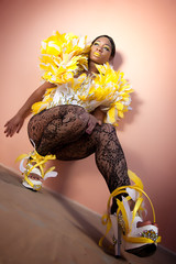 Female Against the Wall with High Heals Wearing Feather Outfit