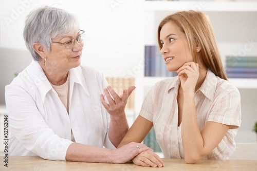 Young woman and grandmother chatting at home