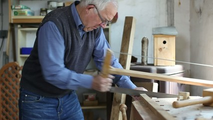 älterer mann sägt holzbalken in der werkstatt