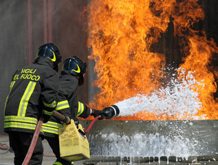 Firefighters extinguish a large fire with a fire extinguisher