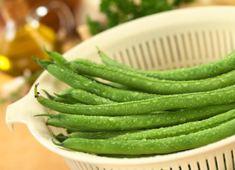 Fresh raw green beans in plastic strainer