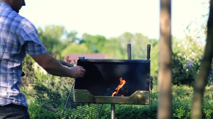 Man preparing grill, outdoors, dolly shot