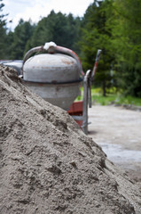 Concrete mixer and sand next to the gravel road
