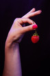 closeup of woman hand with strawberry against dark background