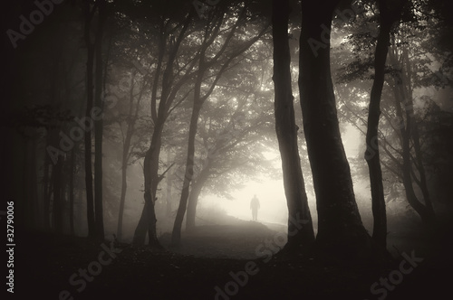 strange figure of a man person walking in a dark forest with fog