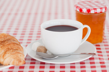 Continental breakfast with croissant, jam and coffee on a tablec