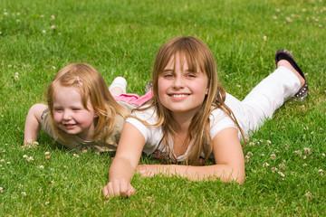 Zwei Schwestern liegend auf der Wiese
