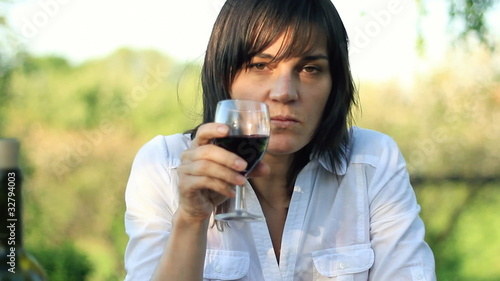 Pensive woman drinking wine, outdoors