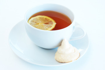 Cup of tea with lemon and meringue cookie