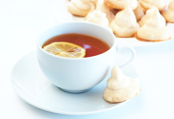 Cup of tea with lemon and meringue cookies