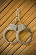 metal handcuffs hanging on the wooden wall.