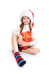 Little girl with santa's hat. Sitting and holding the gift