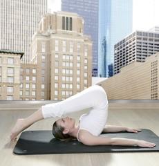 black mat yoga woman window view city urban buildings